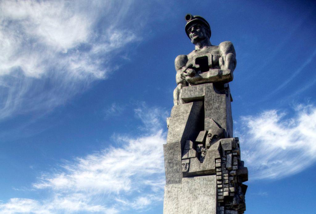 Памятник представляет собой гигантский бронзовый торс шахтера, установленный на трехметровом постаменте из черного гранита